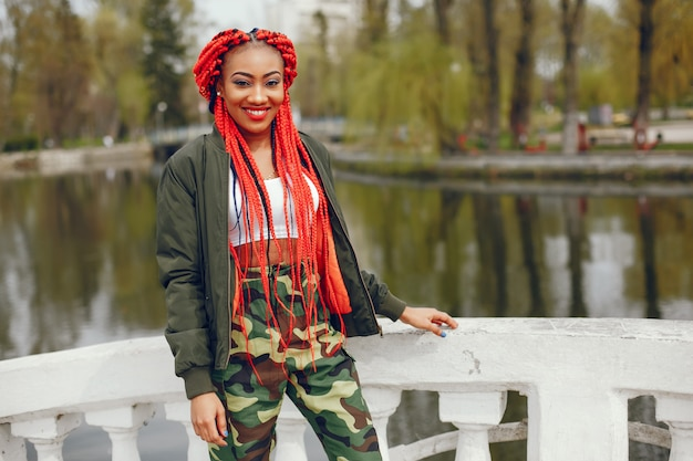 A young and stylish dark-skinned girl with red dreads walking in the summer park near river