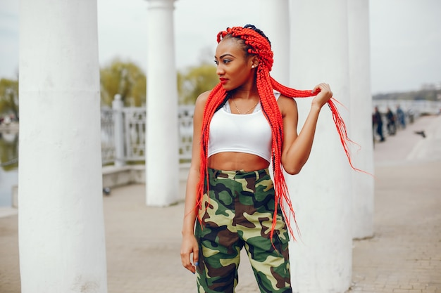 A young and stylish dark-skinned girl with red dreads walking in the summer park