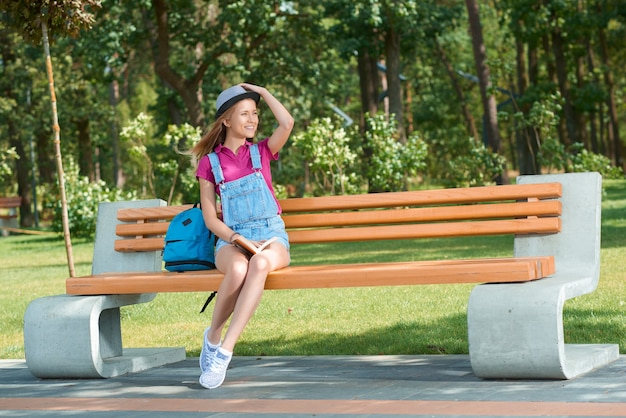 책을 들고 벤치에 앉아 젊은 세련 된 옷을 입고 소녀