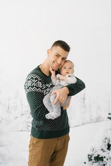 Молодой стильный отец держит сына на руках.