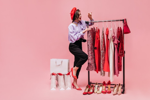 Young stylish girl in black trousers, blouse and red hat is looking at shiny dresses while shopping on pink background.