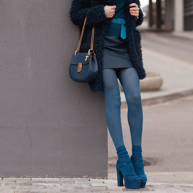 Young stylish girl in blue coat and blue clothes posing