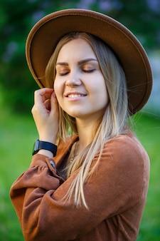 庭のピンクのライラックの緑豊かな茂みの近くの帽子の若いスタイリッシュな女の子。女の子はライラックの香りを楽しんでいます。彼女の顔に笑顔で庭の若い女性の暖かい夏の日