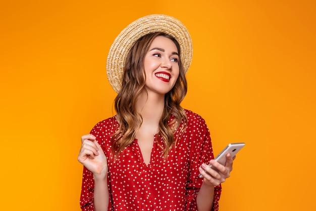 Молодая стильная девушка в красном винтажном платье соломенной шляпе с красной помадой улыбается, смеется, слушает музыку на мобильном телефоне и смотрит на желтую оранжевую стену