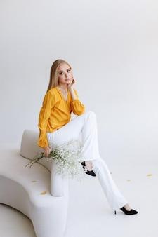 ドライフラワー秋の気分で明るいインテリアでファッショナブルな服を着た若いスタイリッシュな女の子