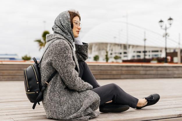 Молодая стильная девушка в сером пальто и очках сидит на улице, пасмурная погода, уличный стиль