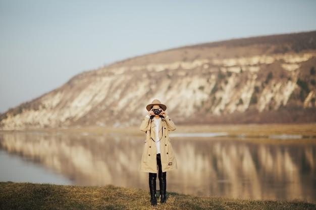 모자와 트렌치 코트에 세련된 소녀가 산과 강이있는 레트로 카메라에 사진을 찍습니다.