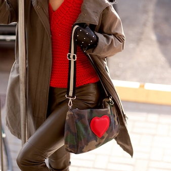 Young stylish girl in leather pants, a red sweater and in the hands of a bright bag