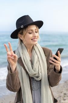 笑顔で顔の時間のビデオ通話をし、ビーチで彼女の腕で平和のジェスチャーを示すスタイリッシュな少女