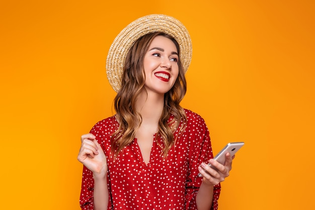 Young stylish girl in a red vintage dress a straw hat with red lipstick smiles laughs listens to music on the mobile phone and looks at  isolated on a yellow an orange wall