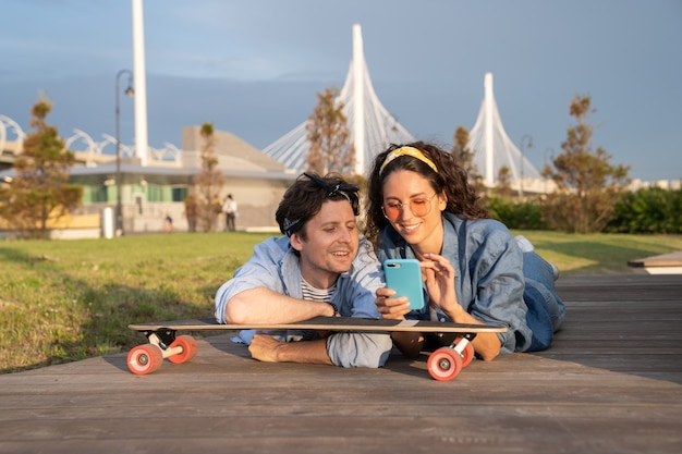 Young stylish girl show guy text message on smartphone lying on longboard in urban park outdoors