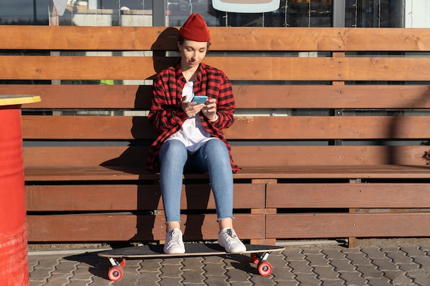 Young stylish girl skater chatting in smartphone outdoors sitting on bench after longboard riding