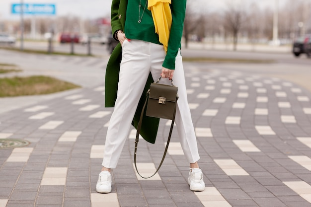 Young, stylish girl in white trousers, warm greens coat