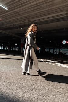 곱슬머리에 부츠를 신은 세련된 긴 코트를 입은 세련된 소녀가 화창한 날 도시를 산책합니다. 여성스러운 도시 스타일과 아름다움