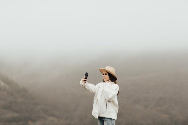 모자와 함께 세련 된 소녀는 아침에 안개가 아름 다운 산의 배경에 셀카를 가져 가라.