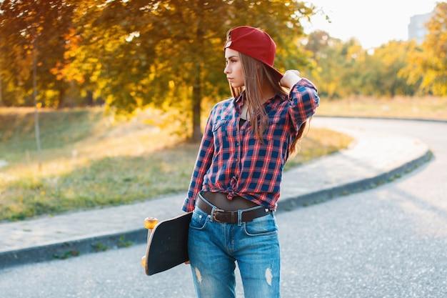 Молодая стильная девушка со скейтбордом