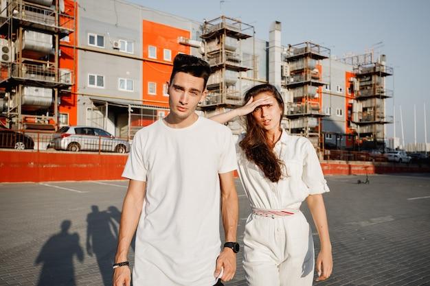 젊은 세련된 남자와 여자는 따뜻한 날에 도시 건물의 배경에 거리에 서 있습니다.