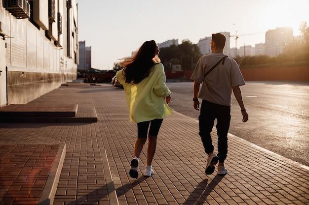 젊고 세련된 남자와 여자가 일몰에 건물 옆에 주차하기 위해 광장에서 함께 걷고 있습니다.