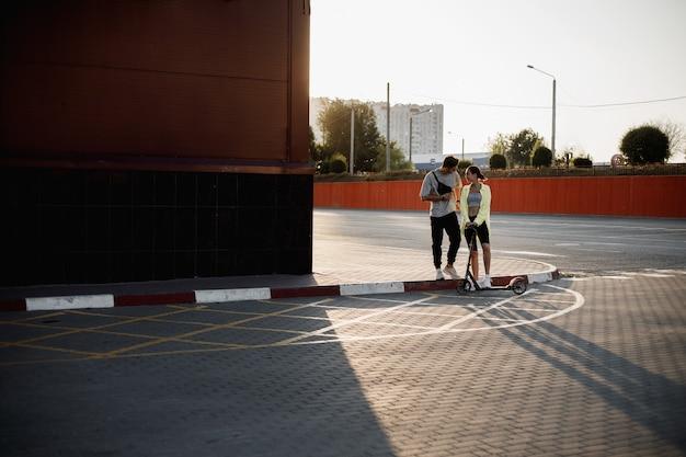 스쿠터를 탄 젊고 세련된 남자와 소녀가 화창한 날 주차를 위해 광장에 함께 서 있습니다.