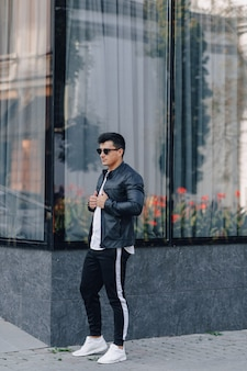 Young stylish guy in glasses in black leather jacket on glass background