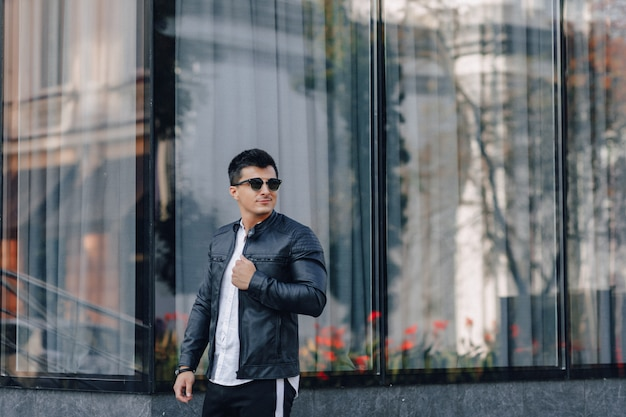 Young stylish guy in glasses in black leather jacket on glass