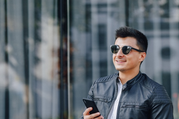 Young stylish guy in glasses in black leather jacket with phone on glass background
