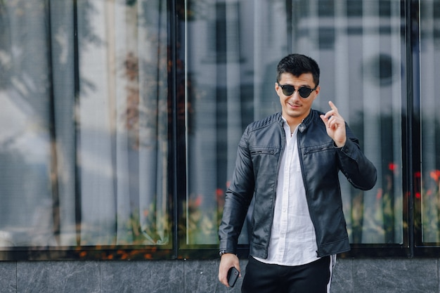 Young stylish guy in glasses in black leather jacket with phone on glass