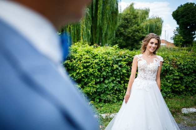 スーツを着た若いスタイリッシュな男新郎と新婦の美しい女の子が白いドレスを着て電車で結婚式の日に公園を散歩