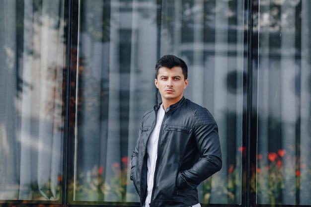 ガラスの背景に黒い革のジャケットのガラスのスタイリッシュな若者