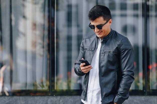 ガラス上の電話で黒い革のジャケットのガラスのスタイリッシュな若者