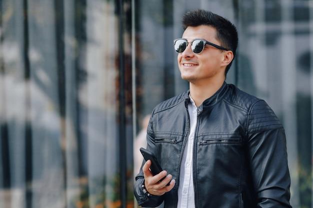 電話で黒い革のジャケットのメガネのスタイリッシュな若者