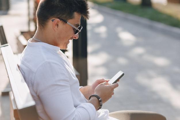 晴れた暖かい日の屋外でベンチに電話でシャツの若いスタイリッシュな男