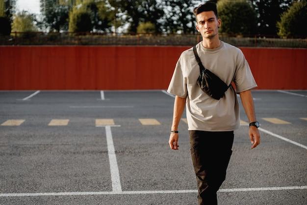 젊은 세련된 남자가 화창한 날 주차를 위해 광장을 걷고 있습니다.