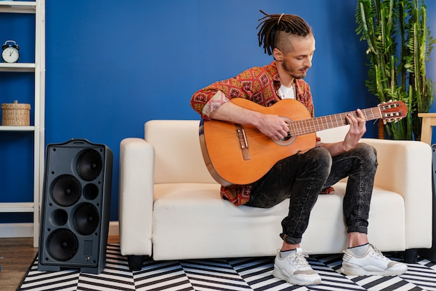 Young stylish guy musician playing guitar in his apartment