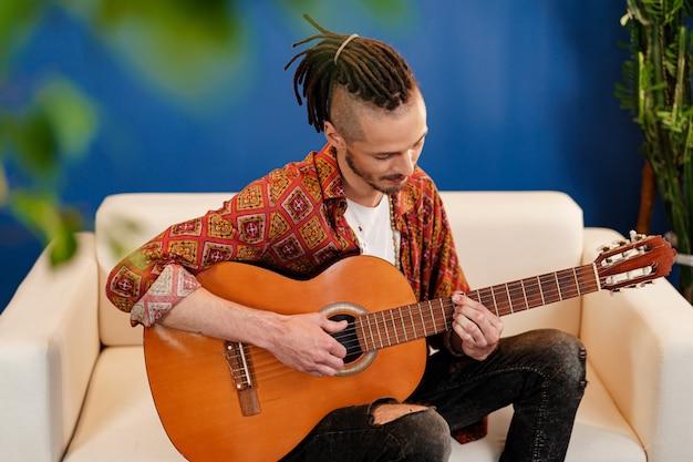 彼のアパートでギターを弾く若いスタイリッシュな男のミュージシャン