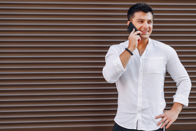 Young stylish guy in shirt talking by phone on simple background