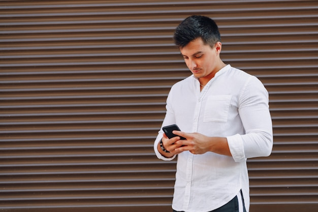 Young stylish guy in shirt typing on phone on simple background