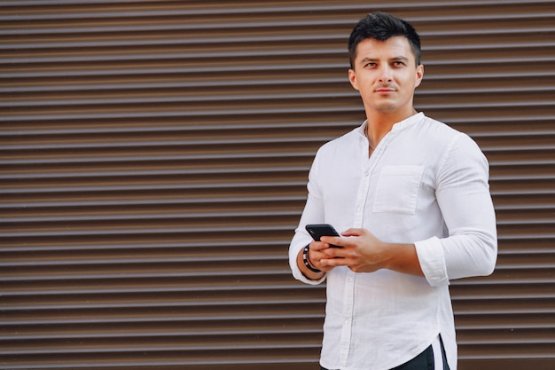 Young stylish guy in shirt typing on phone on simple
