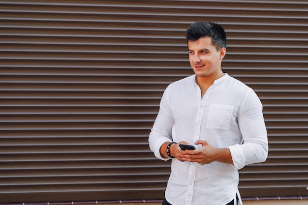 Young stylish guy in shirt typing on phone