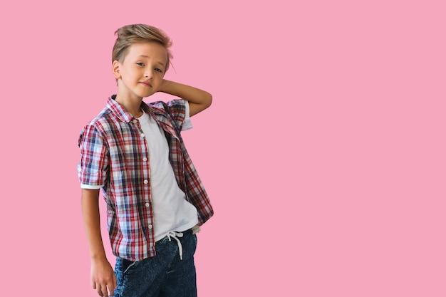 Молодой стильный красивый ребенок улыбается в белой футболке
