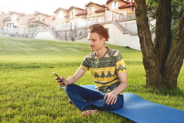 若いスタイリッシュなハンサムな男は草の上に座って、公園で休んでいる電話で話している。