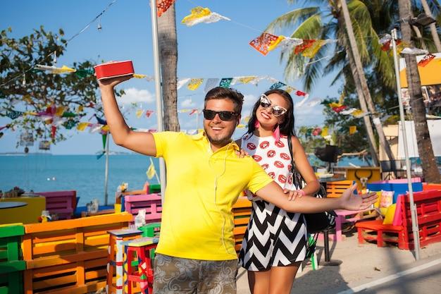 タイの夏休みに若いスタイリッシュな流行に敏感な美しいカップル、軽薄、ファッショントレンドの衣装、サングラス、トロピカルロマンス、笑顔、幸せ、音楽を聴く、パーティー気分、ビーチカフェ