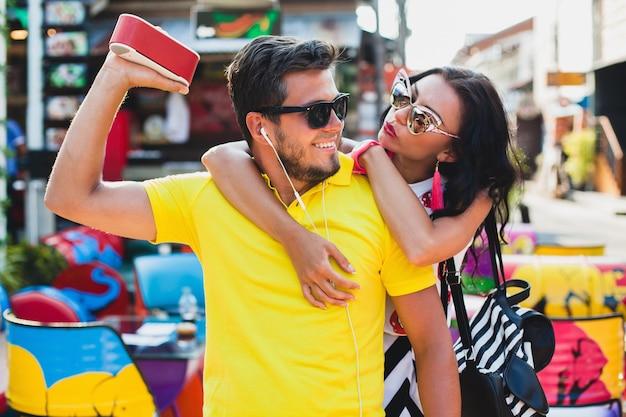 カラフルなカフェに座っている若いスタイリッシュな流行に敏感な美しいカップル、軽薄、ファッションの服、流行の服、サングラス、熱帯の休暇、休日のロマンス、新婚旅行、笑顔、幸せ、音楽を聴く