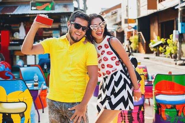 Giovane coppia alla moda hipster bella seduta al caffè colorato, flirty, vestito di moda, vestito alla moda, occhiali da sole, vacanza tropicale, romanticismo natalizio, luna di miele, sorridente, felice, ascoltando musica