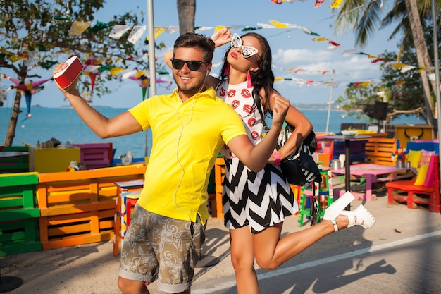Young stylish hipster beautiful couple on summer vacation in thailand, flirty, fashion trend outfit, sunglasses, tropical romance, smiling, happy, listening music, party mood, beach cafe