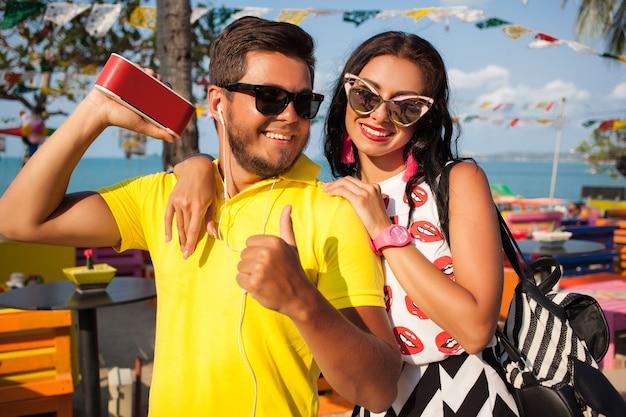 Giovane coppia alla moda hipster bella in vacanza estiva in thailandia, flirty, vestito di tendenza di moda, occhiali da sole, romanticismo tropicale, sorridente, felice, ascoltare musica, atmosfera di festa, bar sulla spiaggia