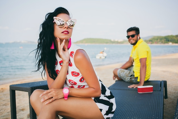 Young stylish hipster beautiful woman sitting on beach, flirty, sexy, hot, fashion outfit, trendy sunglasses, tropical vacation, holiday romance, honey moon, man on background looking, smiling, happy