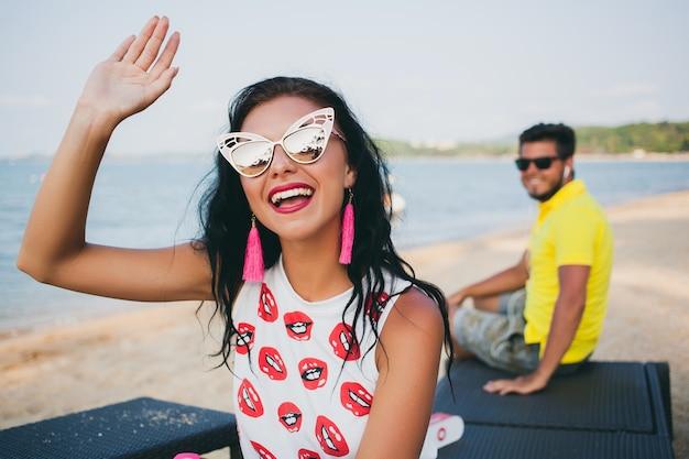 ビーチに座っている若いスタイリッシュな流行に敏感な美しい女性、軽薄、セクシー、ホット、ファッションの衣装、流行のサングラス、熱帯の休暇、休日のロマンス、背景を探して、笑顔、手を振って男