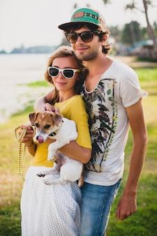 Молодая стильная хипстерская влюбленная пара держит собаку в тропическом парке, улыбается и веселится во время отпуска, в темных очках, кепке, желтой рубашке с принтом