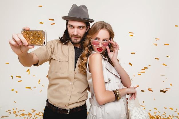 Молодая стильная хипстерская влюбленная пара, делающая самостоятельное фото, празднуя дискотеку, веселится